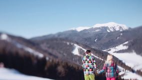 一身桃红色滑雪穿戴的女孩和一套绿色冬季体育服装的英俊的年轻人 可爱的夫妇想知道下来 股票视频