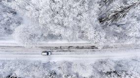 一车辆驾驶通过乡下公路的冬天多雪的森林 顶视图 免版税库存照片