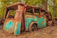 一辆五颜六色的生锈的老运输公共汽车的击毁 免版税图库摄影