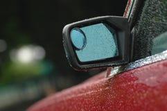 一辆全新的红色汽车的后方镜子在与小滴的雨天 库存照片