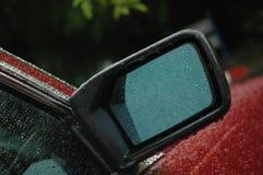 一辆全新的红色汽车的后方镜子在与小滴的雨天 免版税库存图片