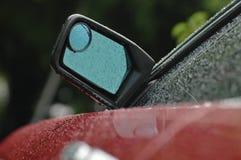 一辆全新的红色汽车的后方镜子在与小滴的雨天 免版税库存照片