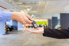 给一辆关键汽车的女实业家商人在汽车停车处 免版税图库摄影