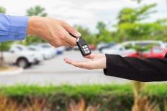 给一辆关键汽车的女实业家商人在汽车停车处 库存照片