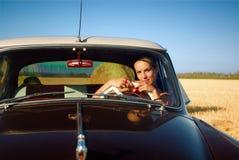 一辆减速火箭的汽车的女孩在夏天领域。 免版税图库摄影