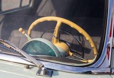 一辆减速火箭的汽车的米黄方向盘通过挡风玻璃是可看见的 免版税库存图片