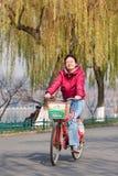 一辆出租自行车的快乐的少妇,杭州,中国 库存图片