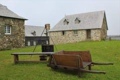 一辆古板的独轮车和烹调封入物Louisbough历史的堡垒的  免版税库存图片