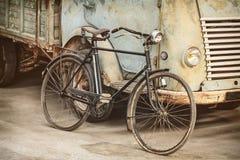 一辆古老自行车和卡车的减速火箭的被称呼的图象 库存照片