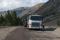 一辆在路和人民的白色卡车立场为路wor做准备 库存照片