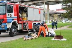 一辆大红火救护车、卡车熄灭火的和男性消防队员准备运转在化学制品,石油 库存照片