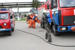 一辆大红火救护车、卡车熄灭火的和男性消防队员准备运转在化学制品,石油 免版税库存图片