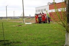 一辆大红火救护车、卡车熄灭火的和男性消防队员准备运转在化学制品,石油 免版税库存照片