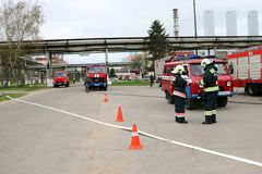 一辆大红火救护车、卡车熄灭火的和男性消防队员准备运转在化学制品,石油 图库摄影