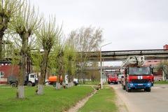 一辆大红火救护车、卡车熄灭火的和男性消防队员准备运转在化学制品,石油 免版税图库摄影