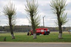 一辆大红火救护车,一辆灭火的卡车,在化学制品,炼油厂乘坐 免版税库存图片