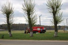 一辆大红火救护车,一辆灭火的卡车,在化学制品,炼油厂在背景中乘坐 免版税库存照片