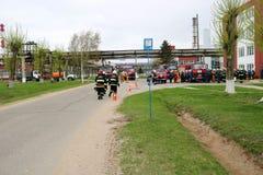 一辆大红火救护车,熄灭火和男性消防队员的卡车在化学制品,反对backgr的炼油厂 免版税库存图片
