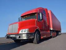 一辆大红色卡车在沥青站立 免版税库存照片