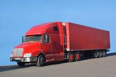 一辆大红色卡车在沥青站立 免版税库存图片