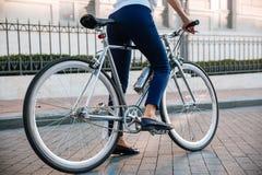 一辆女性骑自行车的人骑马自行车的播种的图象在街道上的 免版税库存图片