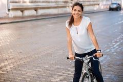 一辆妇女骑马自行车的画象在城市街道的 免版税库存照片