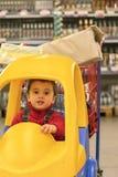 一辆婴儿车的小孩男孩在瓶对面的一个购物中心有酒精的 免版税库存图片
