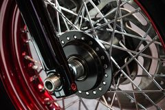 一辆定制的摩托车的黑轮子的细节镀铬与红色和银色轮子 图库摄影