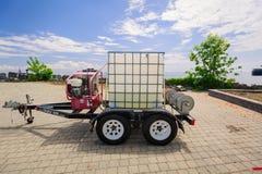 一辆小拖车的特写镜头视图有塑料盒的在金属框架和引擎在拖车框架登上了 库存图片