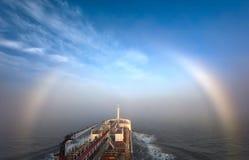 一辆小罐车的弓在有薄雾的彩虹的背景的 免版税库存照片