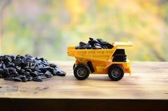 一辆小黄色玩具卡车用向日葵种子装载在小堆向日葵种子旁边 在的一辆汽车木表面agains 免版税库存照片