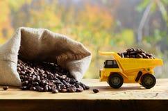 一辆小黄色玩具卡车用在一个充分的袋子的棕色咖啡豆装载五谷附近 木表面上的一辆汽车反对backg 库存图片