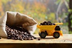 一辆小黄色玩具卡车用在一个充分的袋子的棕色咖啡豆装载五谷附近 木表面上的一辆汽车反对backg 免版税库存图片