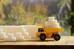 一辆小黄色玩具卡车用在糖墙壁附近的白糖立方体装载 木表面上的一辆汽车反对背景  库存照片