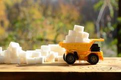 一辆小黄色玩具卡车用在糖残骸附近的白糖立方体装载 木表面上的一辆汽车反对背景o 库存照片