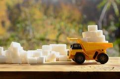 一辆小黄色玩具卡车用在糖残骸附近的白糖立方体装载 木表面上的一辆汽车反对背景o 免版税库存图片
