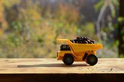 一辆小黄色玩具卡车用棕色咖啡豆装载 木表面上的一辆汽车反对秋天森林Extr背景  库存图片
