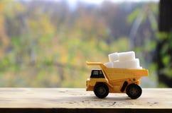 一辆小黄色玩具卡车用白糖立方体装载 木表面上的一辆汽车反对额外秋天森林的背景  库存图片