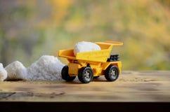 一辆小黄色玩具卡车用白色盐石头装载在堆盐旁边 木表面上的一辆汽车反对backgro 库存图片