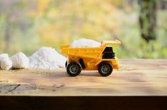 一辆小黄色玩具卡车用白色盐石头装载在堆盐旁边 木表面上的一辆汽车反对backgro 免版税库存图片