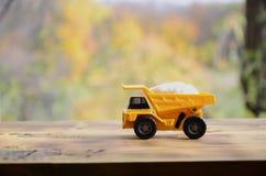 一辆小黄色玩具卡车用白色盐石头装载 木表面上的一辆汽车反对秋天森林E背景  免版税库存照片