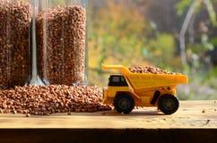 一辆小黄色玩具卡车用荞麦和一杯棕色五谷在荞麦堆附近的装载义膜性喉炎 在木头的一辆汽车 免版税库存照片