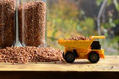 一辆小黄色玩具卡车用荞麦和一杯棕色五谷在荞麦堆附近的装载义膜性喉炎 在木头的一辆汽车 库存照片