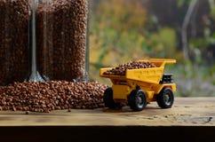 一辆小黄色玩具卡车用荞麦和一杯棕色五谷在荞麦堆附近的装载义膜性喉炎 在木头的一辆汽车 库存图片