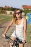 一辆愉快的深色的女孩骑马自行车的画象在黏土奔跑的 免版税库存图片