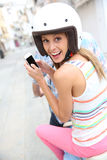 一辆摩托车的快乐的妇女有智能手机的 库存图片