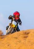 一辆摩托车的男孩竟赛者在沙漠 免版税库存照片