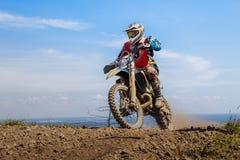 一辆摩托车的竟赛者在山顶部 库存图片