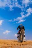 一辆摩托车的竟赛者在沙漠 免版税库存照片