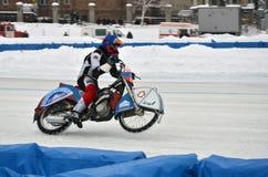 一辆摩托车的竟赛者有在后轮的峰值的 免版税库存图片
